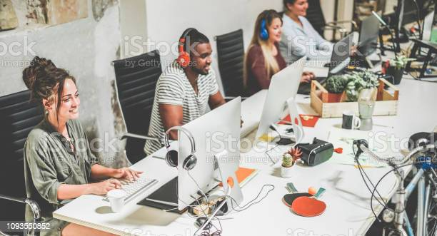 Young Trendy Teamwork Using Computer In Creative Coworking Office Business People Working Together At New App Project Focus On Left Woman Face Technology Influencer Marketing And Job Concept Stock Photo - Download Image Now