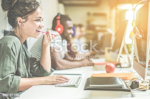 istock Young trendy teamwork using computer in creative office - Business people working together at web site project - Focus on woman right hand - Technology job concept - Contrast retro filter 699181156