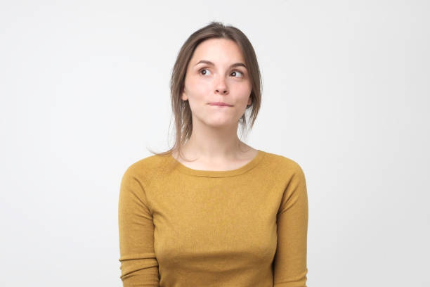Young tricky woman having something in mind with sly facial expression Young tricky woman having something in mind with sly facial expressions, over gray background embarrassment stock pictures, royalty-free photos & images