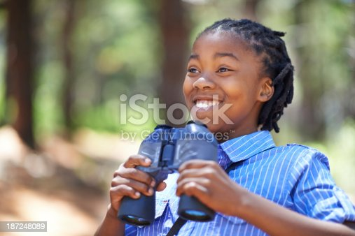 Shot of a happy-looking young boy out in the woods with a pair of binoculars