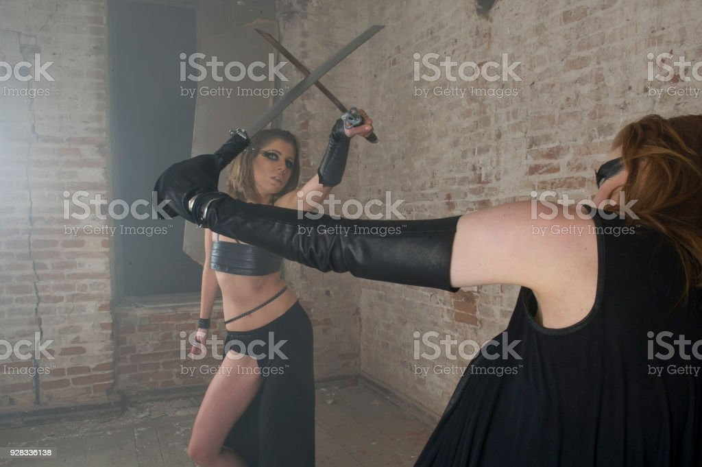 young two women fighting with sword in ruined building