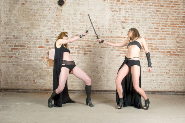 young two women fighting with sword stock photo