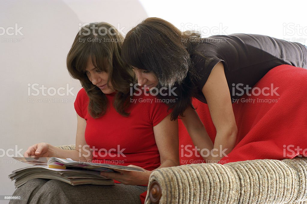 young two women in reading magazine royalty-free stock photo