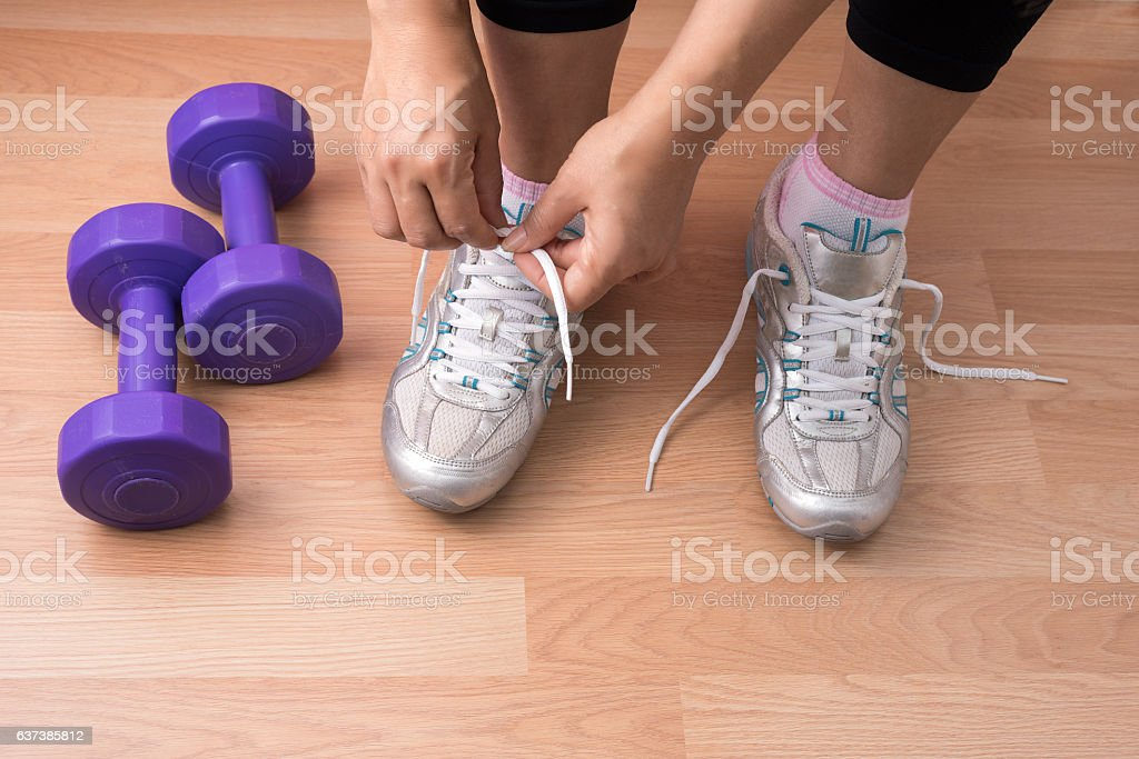 Young tying her shoelaces stock photo