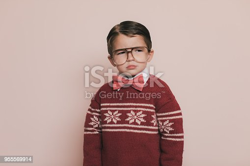 Young Christmas sweater boy with eyeglasses and an ugly sweater makes a frown and looks away from the camera. He is disappointed because he cannot open his gifts and presents at the party. He does not want to go to the Christmas holiday party because it is boring.