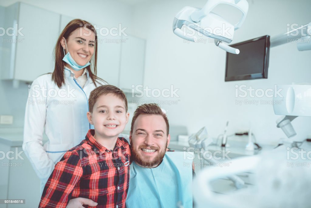 Young Uncle Show His Nephew that Being at Dentist is Not Scary at All stock photo