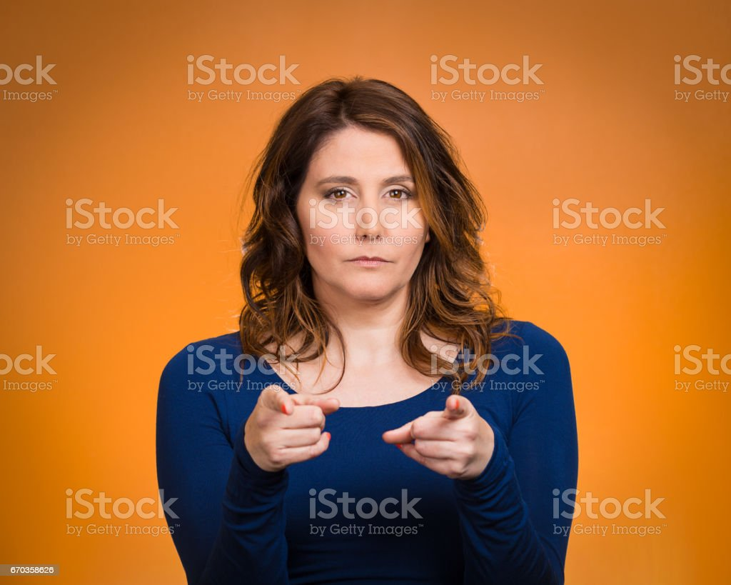 young, unhappy, serious woman pointing finger at someone, blaming for something wrong, mistake, stock photo