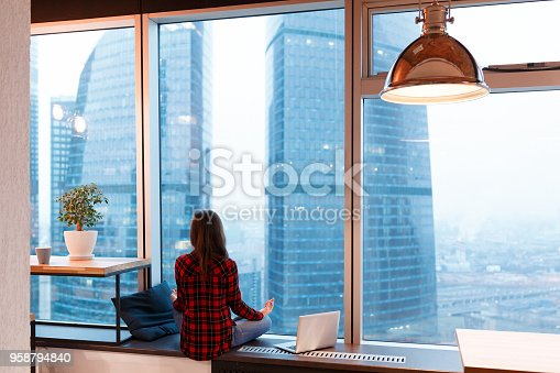 1162297213 istock photo Young unidentified woman freelancer designer in casual clothes admiring the view and meditating during break in the background of window overlooking skyscrapers 958794840