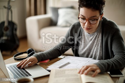 istock Young university student studying at home 1128909047