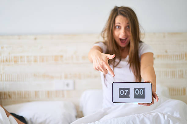 young unkempt woman pointing at vintage flip clock stock photo
