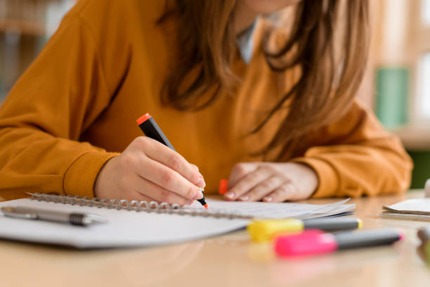 Young unrecognisable female college student in class, taking notes and using highlighter. Focused student in classroom. Authentic Education concept. stock photo