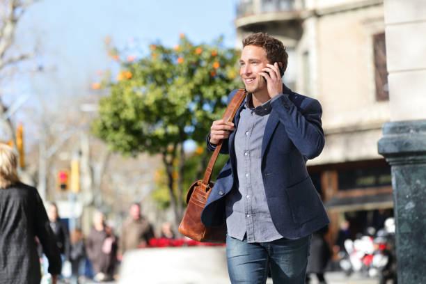 Young urban businessman on smart phone, Barcelona stock photo