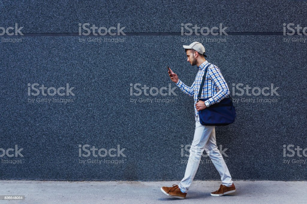 Young urban casual businessman walking and reading messages on smartphone stock photo