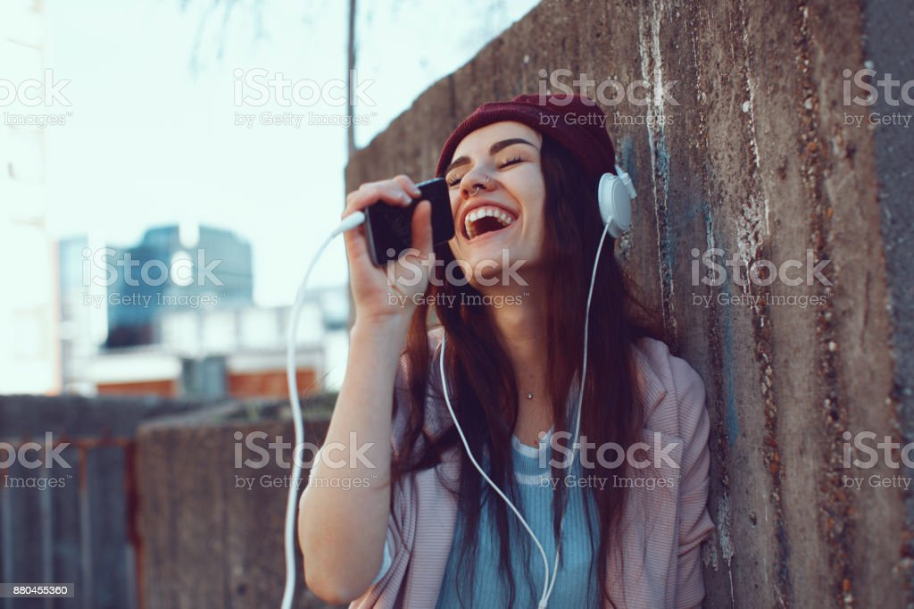 Young urban woman listens to music via headphones and smartphones stock photo
