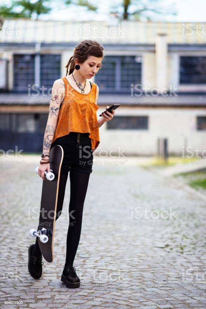 Young urban woman using phone for communication stock photo