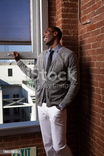 A smiling young African-American urbanite looking out the window of an upper-floor loft apartment.