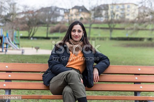 Young urbanite Indian woman sitting on park bench listening to earphones and smiling with confidence.