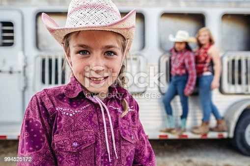 Portrait of a young Utah cowgirl with long braided blonde hair, looking at camera.