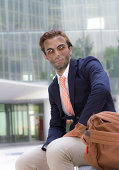Young vampire businessman outside office with backpack in summer has finished his day work and looking away