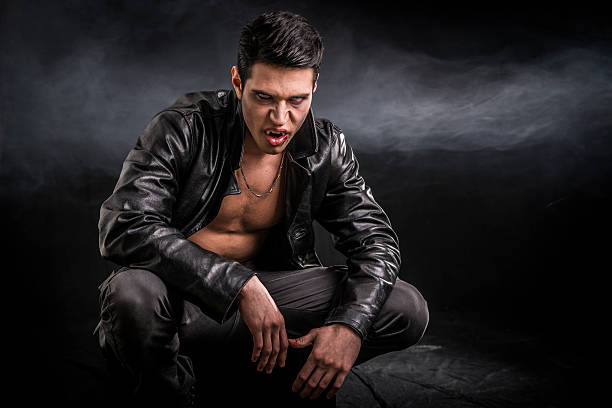 Young Vampire Man in an Open Black Leather Jacket Portrait of a Young Vampire Man in an Open Black Leather Jacket, Showing his Chest and Abs, Looking at the Camera, on a Black Background. fang stock pictures, royalty-free photos & images