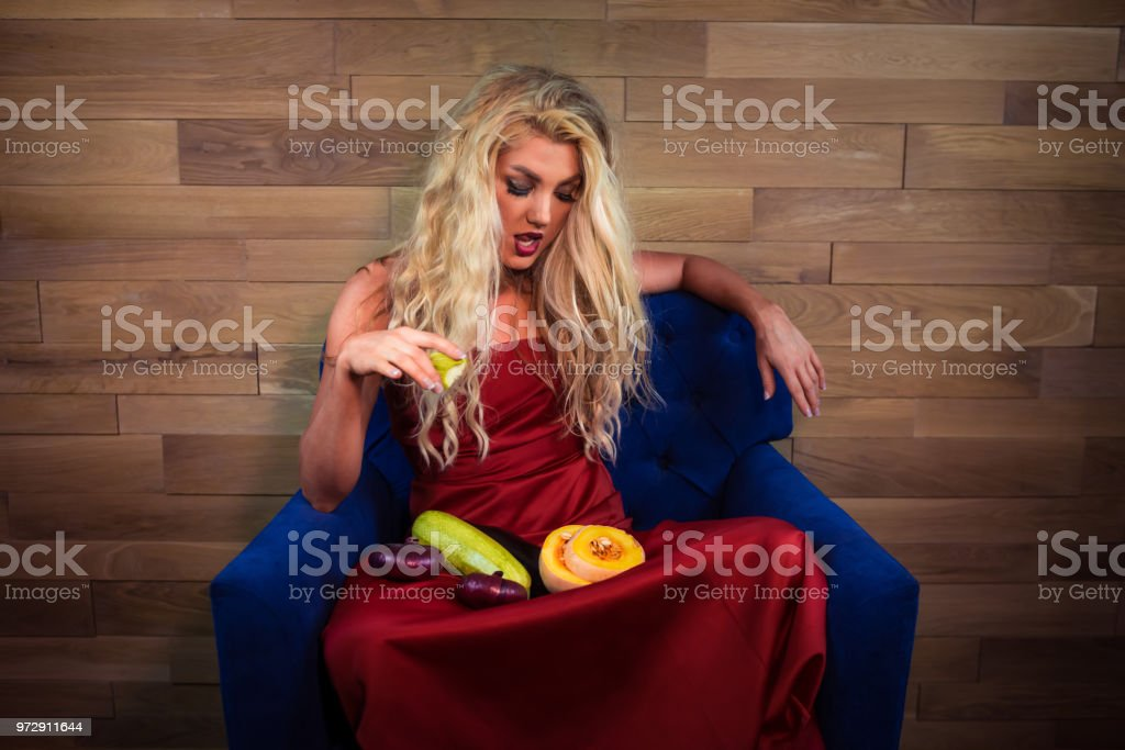 Young vegetarian woman sits with vegetables on armchair on background...