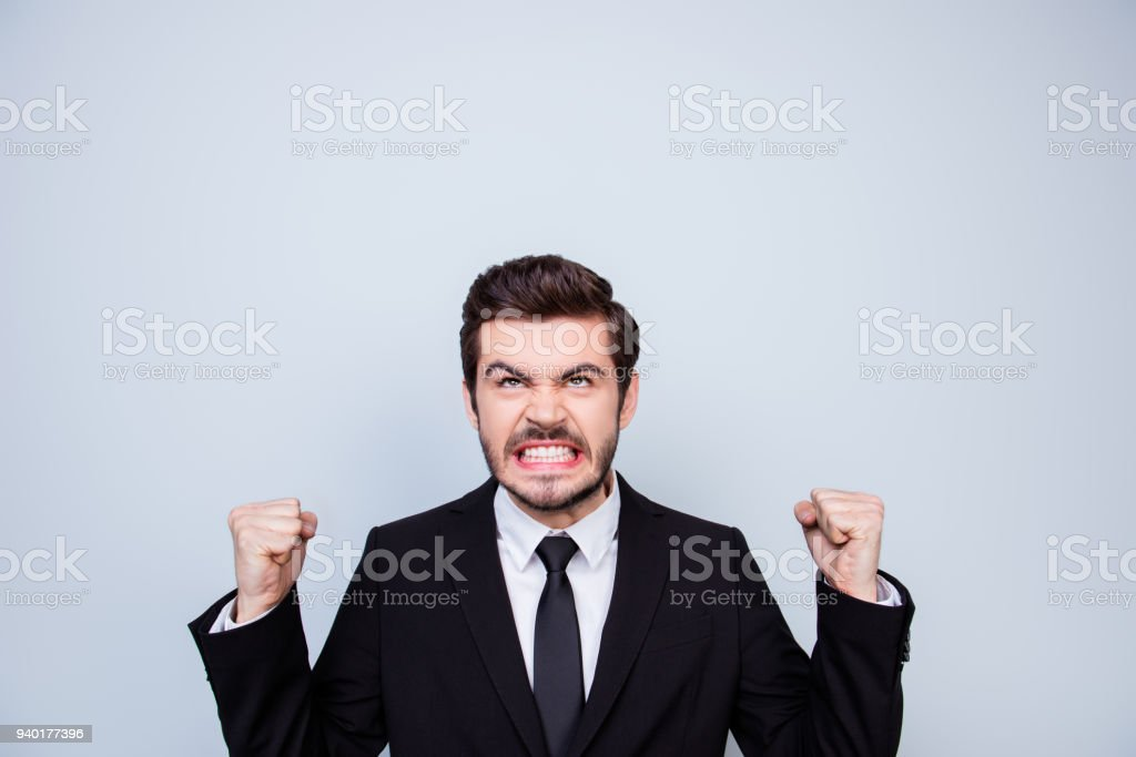 Young very angry man in black suit showing fists and looking up on copyspace over his head in rage stock photo