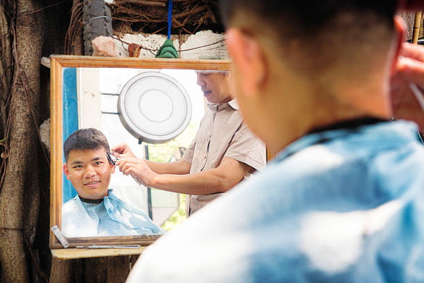 Young vietnamese man appreciative of haircut Young vietnamese man appreciative of haircut being given to him on Hanoi street, Vietnam. Over the shoulder shot looking into mirror. asian barber stock pictures, royalty-free photos & images