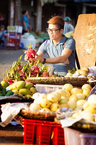 Young Vietnamese man buying pitaya dragonfruit at Hanoi street market