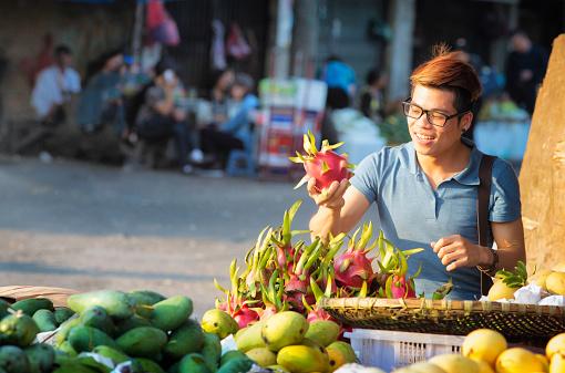 Young Vietnamese man picks up pitaya dragonfruit at street market