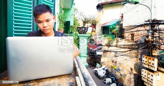 istock Young Vietnamese man working with laptop on Hanoi balcony 605996178