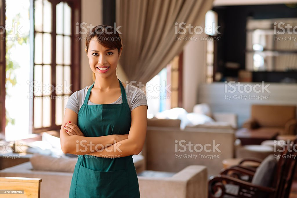 Young Vietnamese waitress smiling with her arms folded stock photo