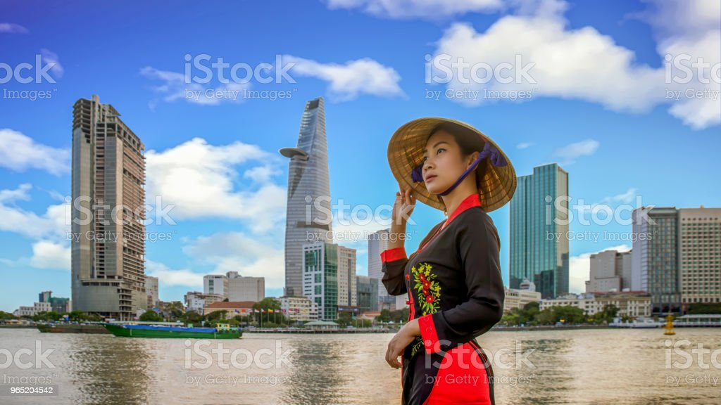 Young vietnamese woman with view of Ho Chi Minh City skyline and the Saigon River, Vietnam royalty-free stock photo