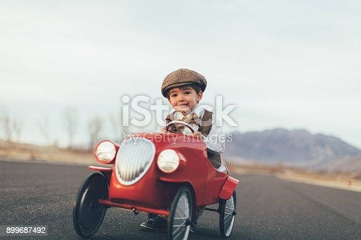 A young boy dressed in vintage vest, bow tie and drivers cap drives his vintage retro-styled red speedster car on a rural road in Utah, USA. He loves to drive his speedster car. Plenty of copy space for your concept.