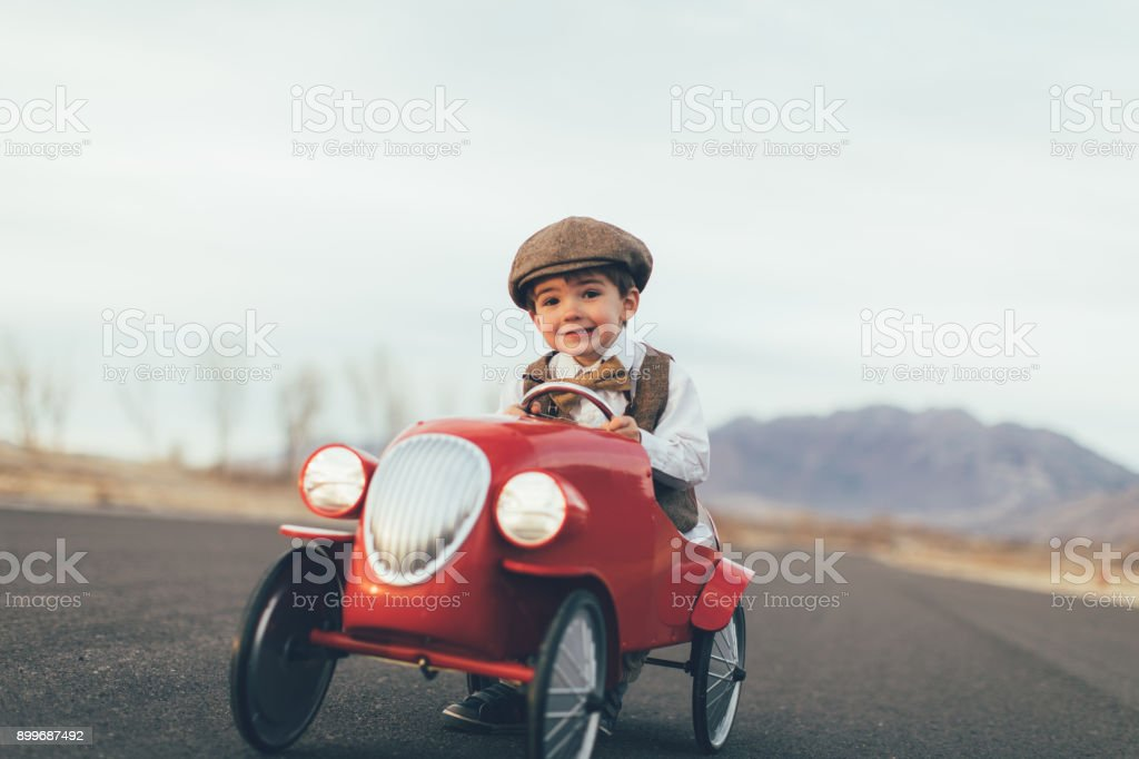Young Vintage Boy Drives Toy Car stock photo