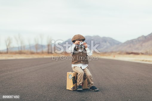 A young boy dressed in an old-fashioned vest, bow tie and driver's cap takes a picture with his camera while sitting on his suitcase on a rural road in Utah, USA. He is ready to go explore the world on his own and take pictures of it while he is gone.