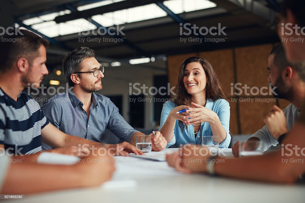 Shot of a group of coworkers having a meeting in an open plan...