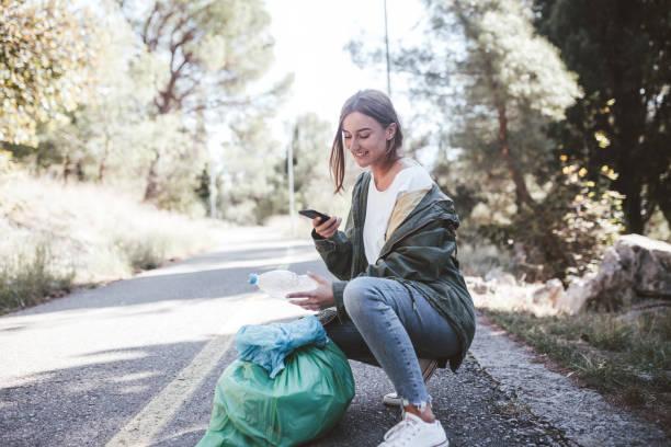 Joven mujer voluntaria está clasificando los residuos plásticos recogidos a través de la aplicación móvil - foto de stock
