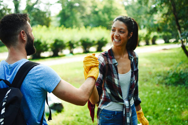 Young volunteers collect garbage in a public park stock photo