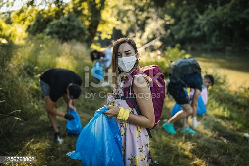 Team of young volunteers cleaning riverbank from trash, girl with face mask in first plan