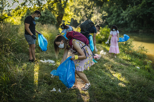 Team of young volunteers cleaning riverbank from trash