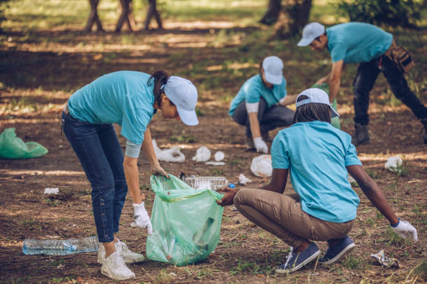 Young volunteers collecting garbage in nature Group of multi-ethnic people, people with differing abilities , volunteers with garbage bags cleaning park area environmental cleanup stock pictures, royalty-free photos & images