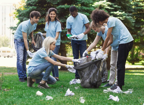 Young volunteers collecting garbage in suumer park stock photo