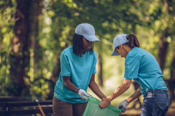 Young volunteers picking up trash Group of multi-ethnic people, people with differing abilities , volunteers with garbage bags cleaning park area environmental cleanup stock pictures, royalty-free photos & images