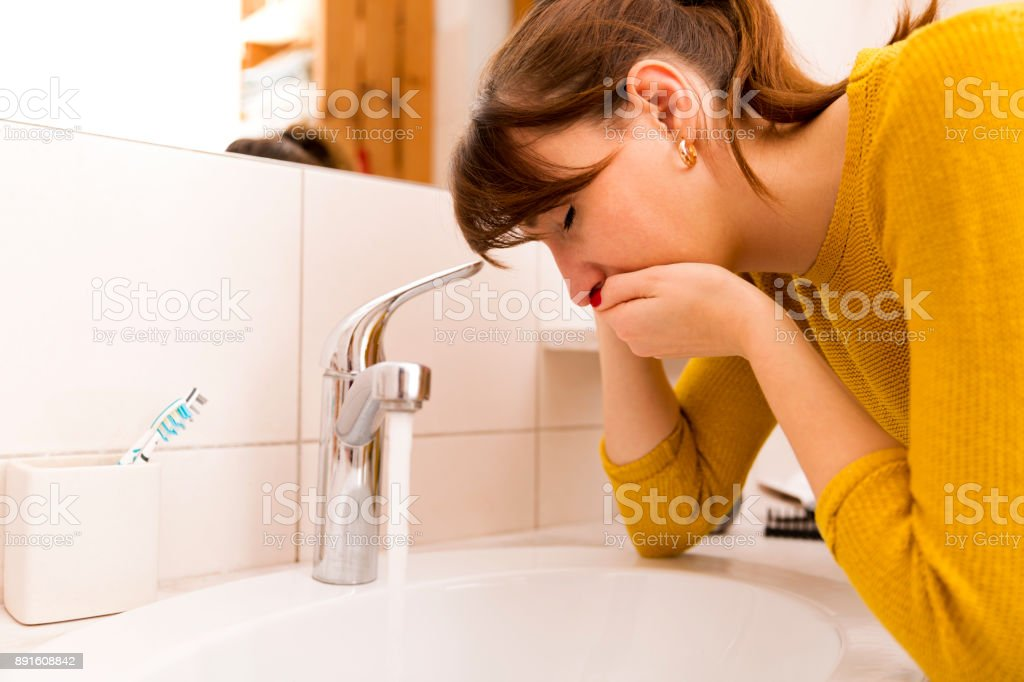 Young vomiting woman near sink in bathroom stock photo