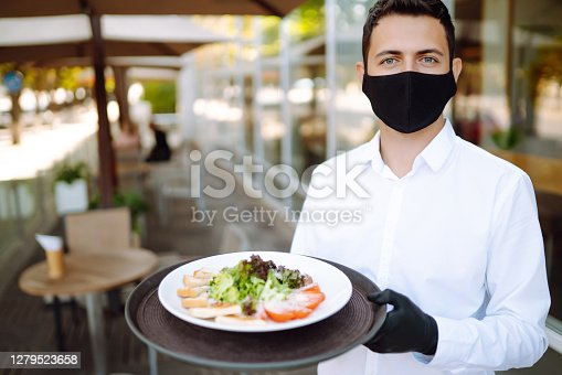 A young waiter in a protective mask on his face and gloves holding plates with salad in the restaurant while working in reopened cafe after coronavirus epidemic. Covid- 2019.