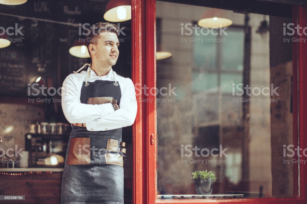 Young waiter is standing at the coffee shop's entry stock photo