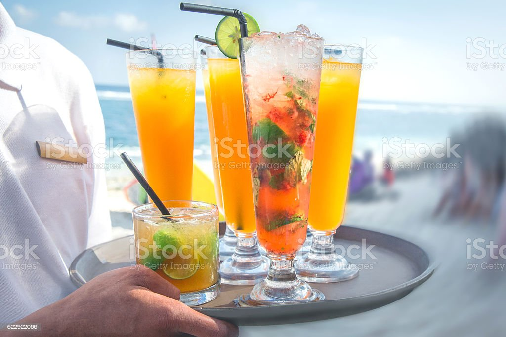 Young waiter serving fruit juices on the beach stock photo