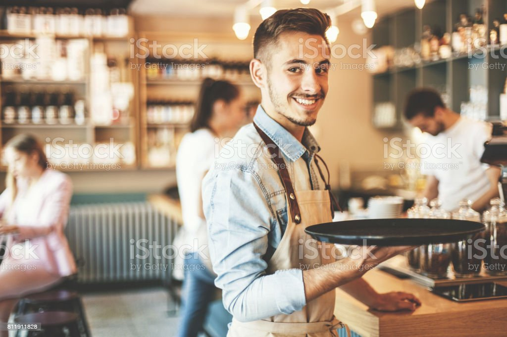 Young waiter serving stock photo