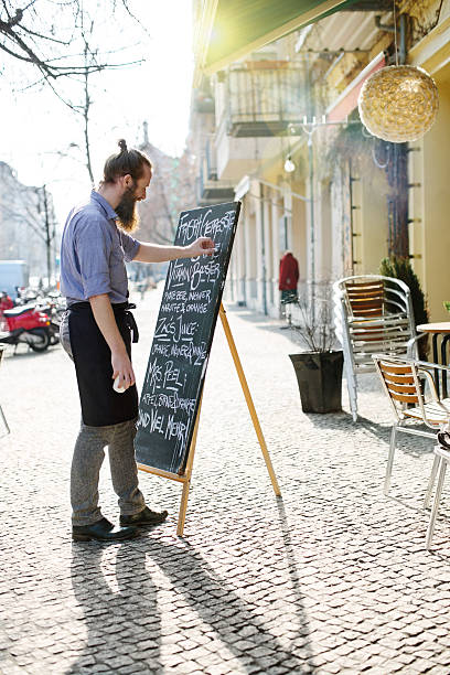 Young waiter updating todays special menu board – Foto