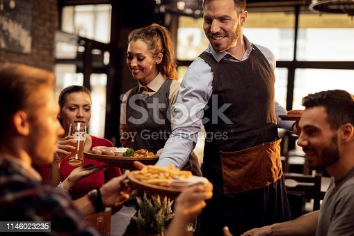 Happy waiters bringing food at the table and serving group of friends in a restaurant.